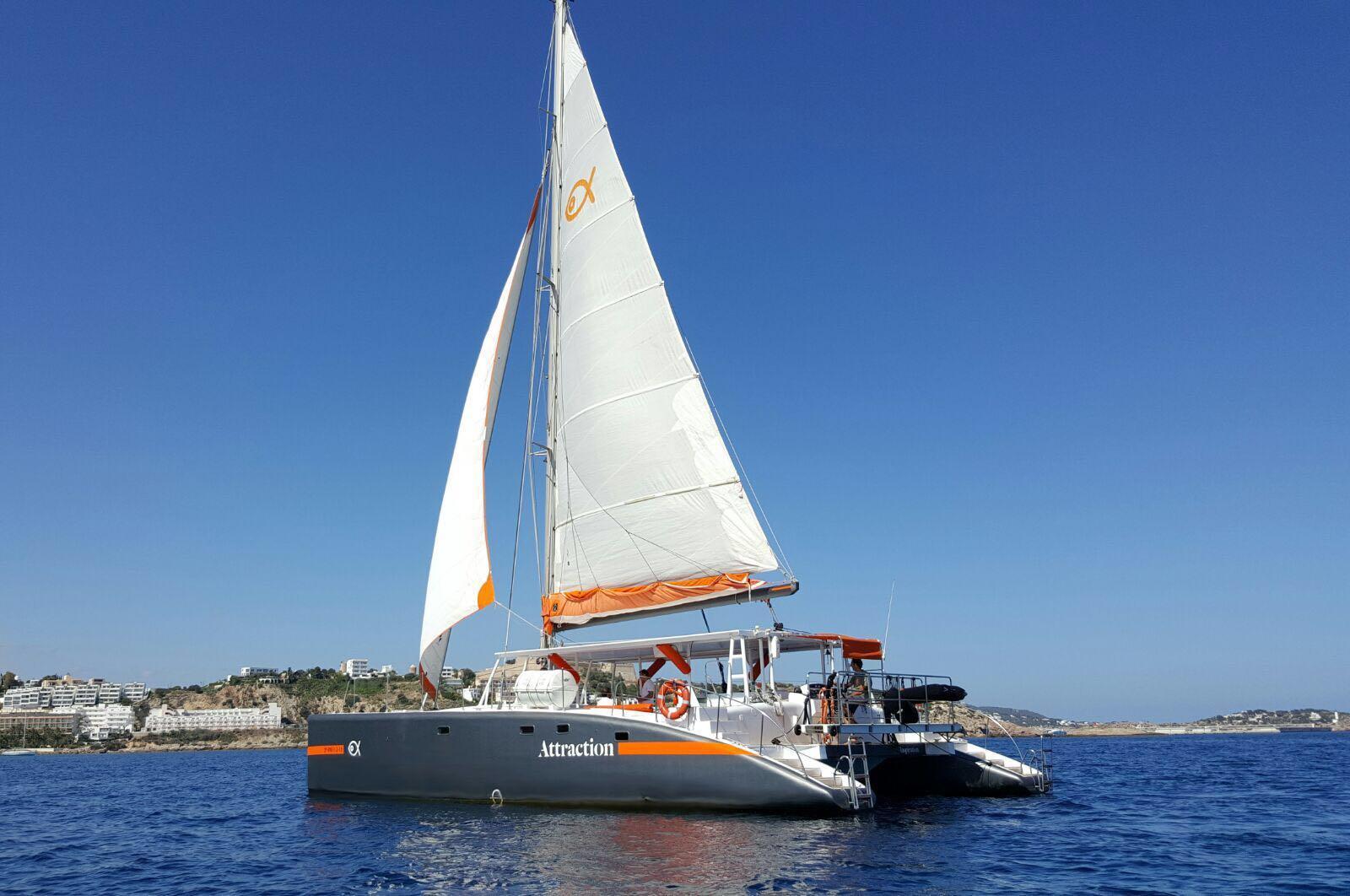 Un elegante catamarán que navega las aguas cristalinas del mar Mediterráneo, para excursiones y eventos privados en las Islas Baleares.